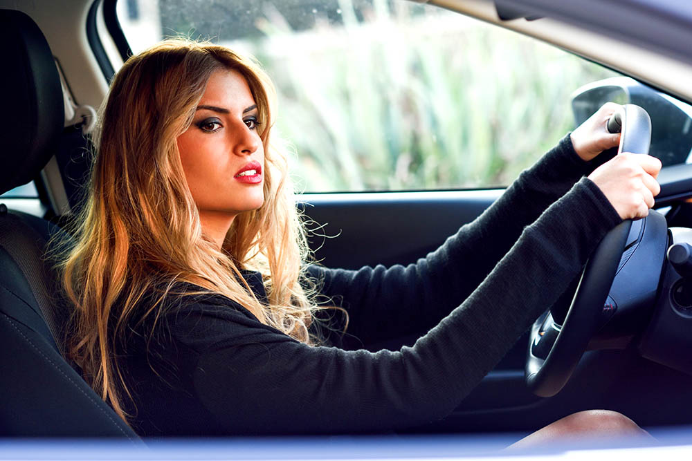 Blond young girl driving a sport car looking at the road